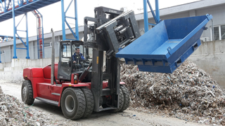 Heavy bales of paper rubbish are transported with the rotating Fork Positioner 15T456.